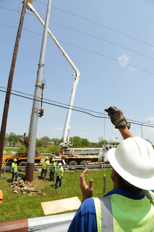 employee supervising pole installation
