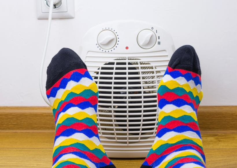 Feet with socks in front of space heater