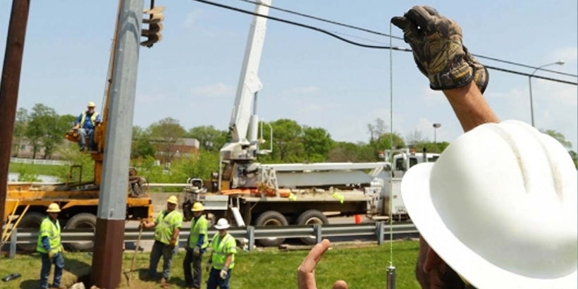 workers installing new power pole