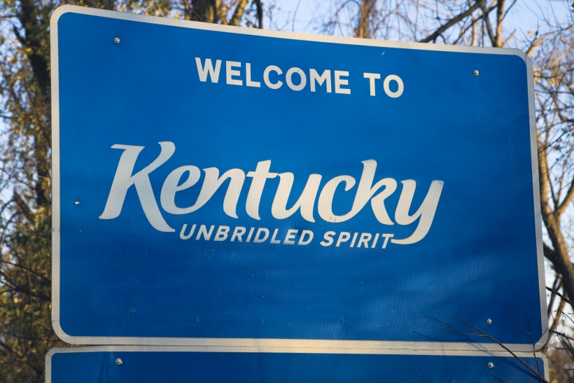 "blue road sign that reads ""Welcome to Kentucky"""