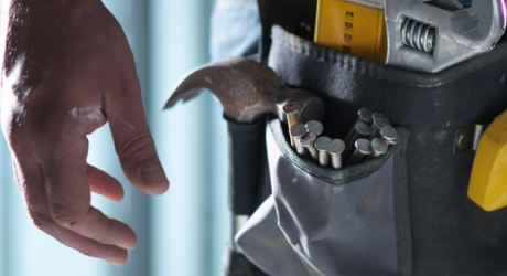 closeup of construction worker's hand and tool belt
