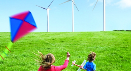 boy and girl with kite in field in front of wind turbines