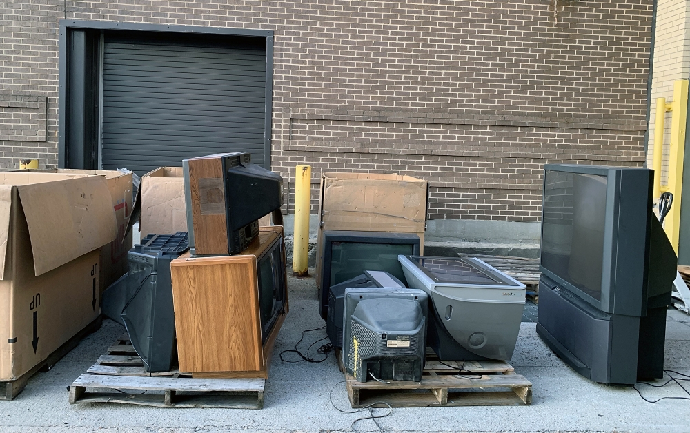loading dock with pallets full of old electronics for recycling