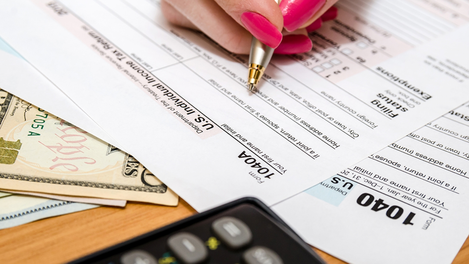 a female hand holding a pen filling out a tax form