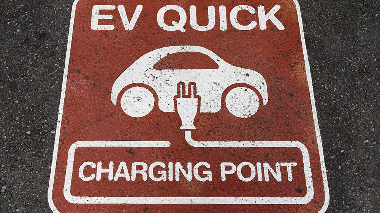 """painted sign on parking lot surface """"EV QUICK charging point"""""""