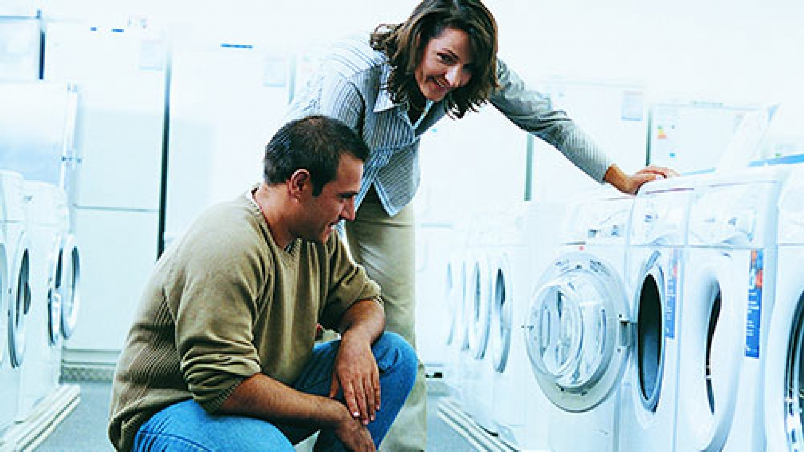 Couple looking at clothes washer in appliance store