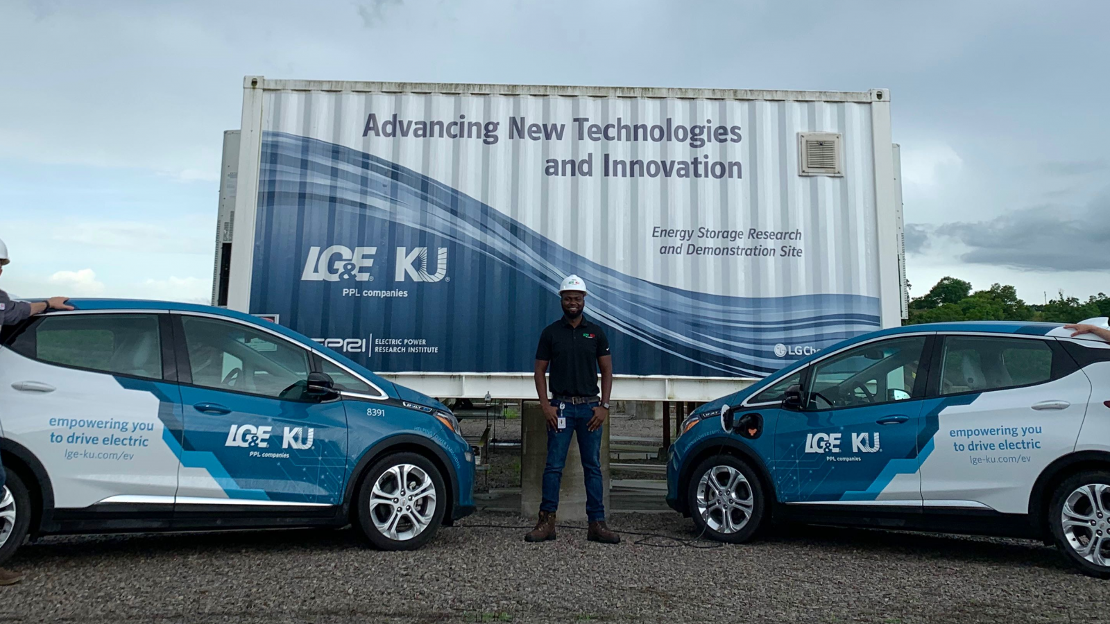 three employees standing next to electric vehicles and large battery storage unit