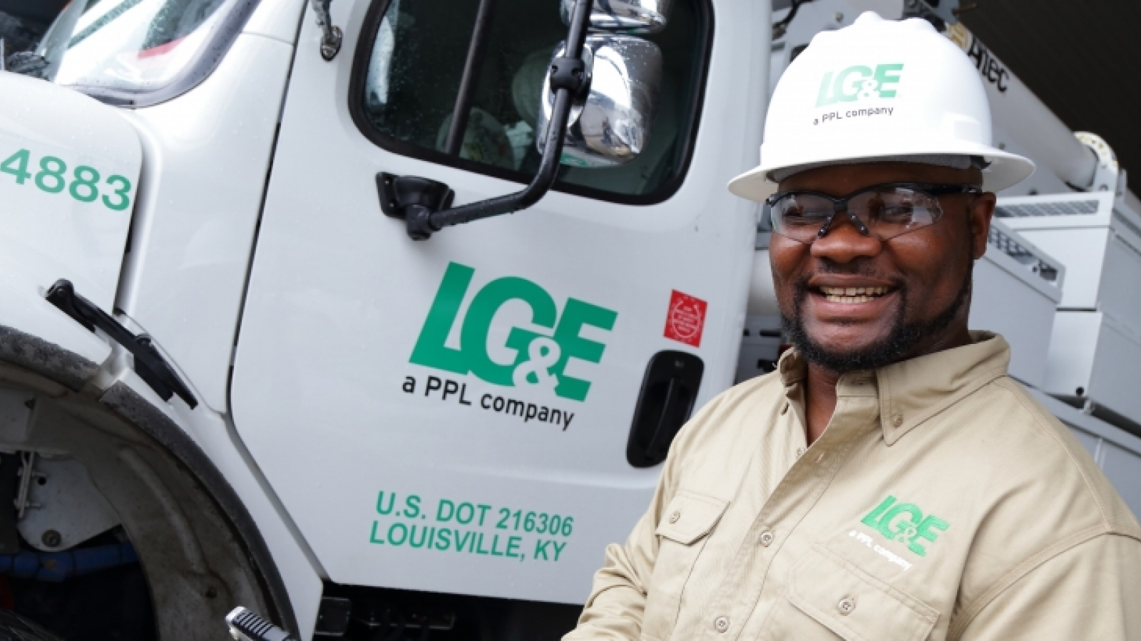 African-American male LG&E employee wearing hardhat standing in front of bucket truck
