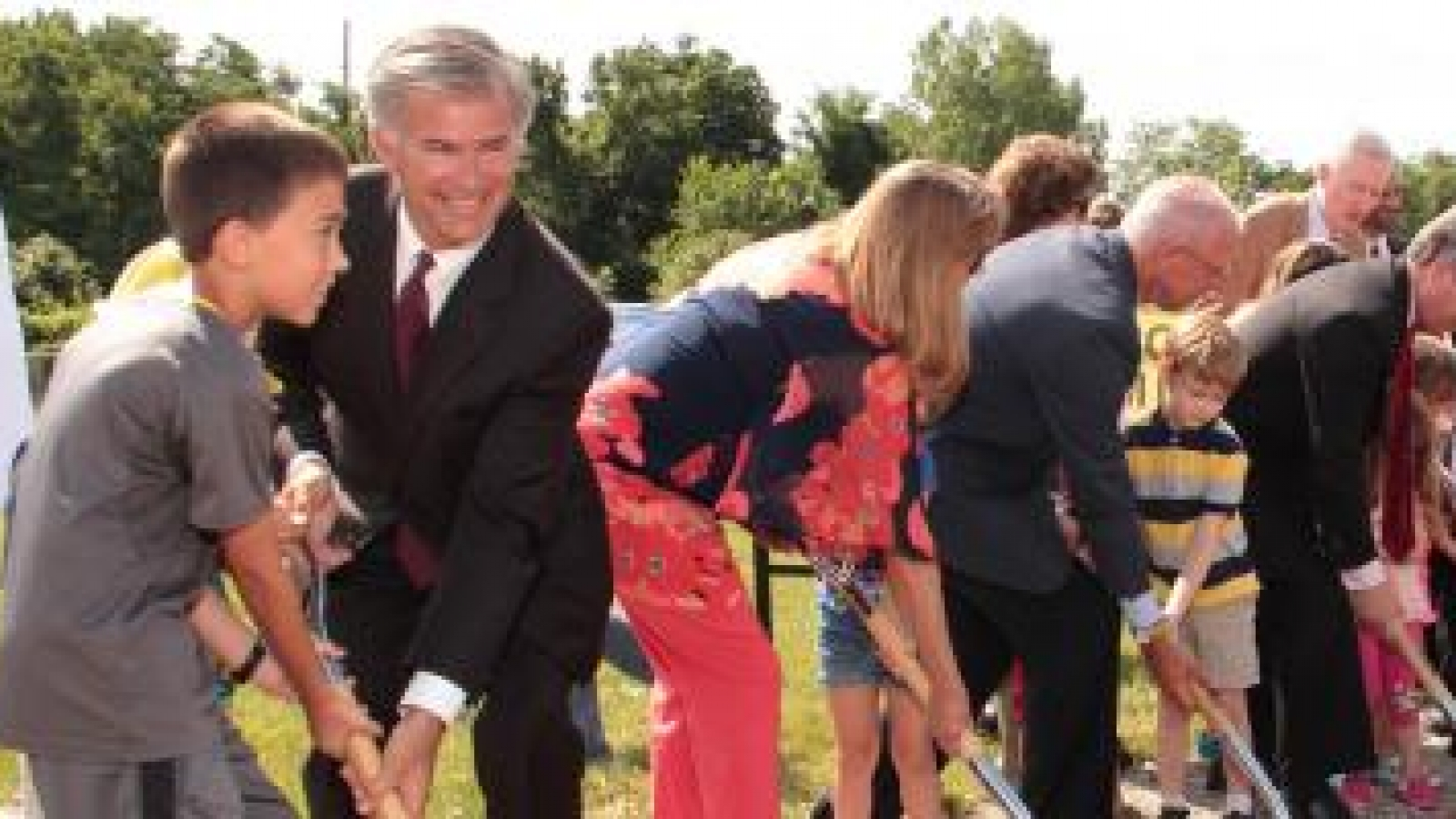 Community groundbreaking ceremony with a row of people with shovels in dirt