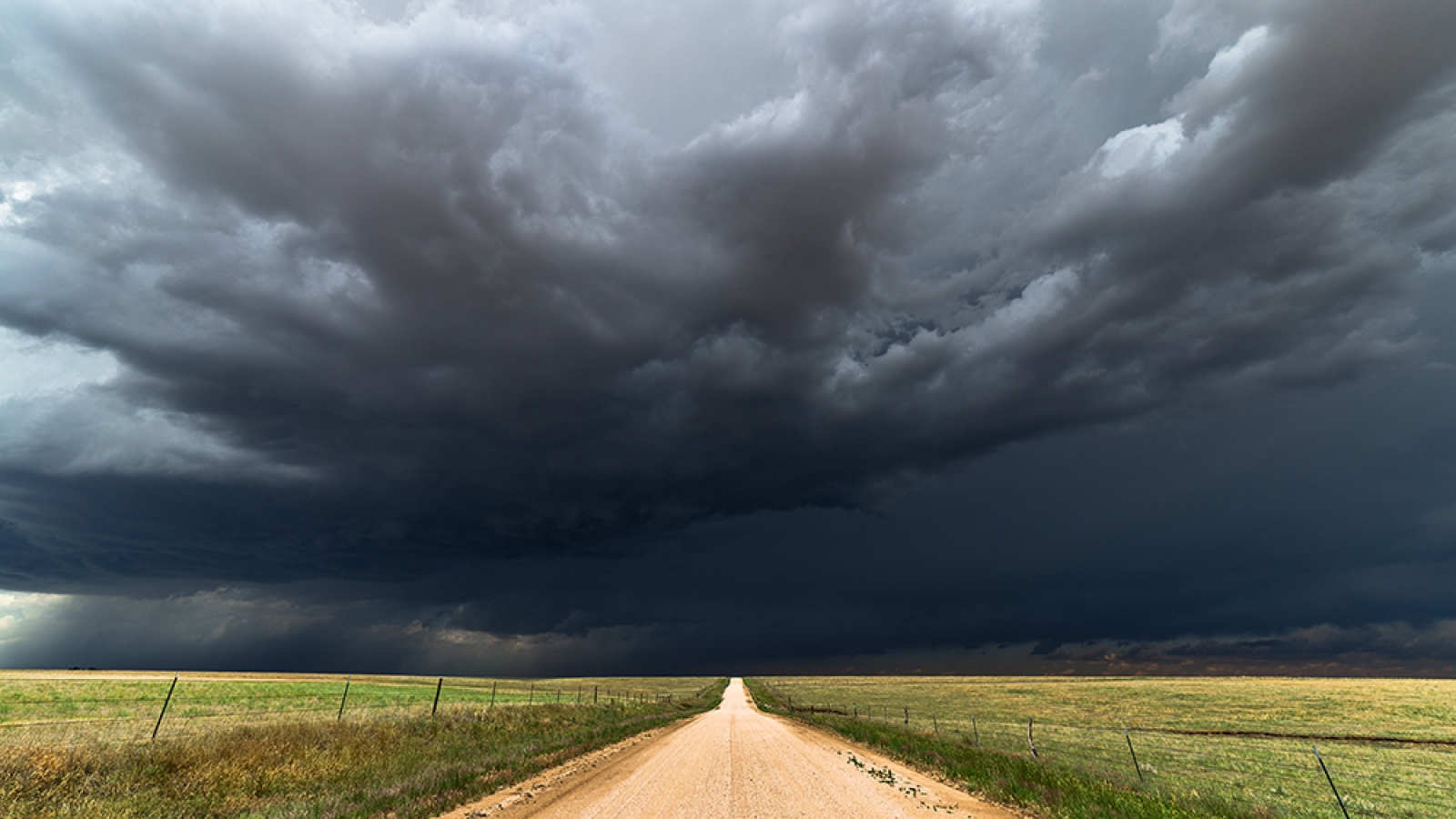 dirt road leading to storm on horizon