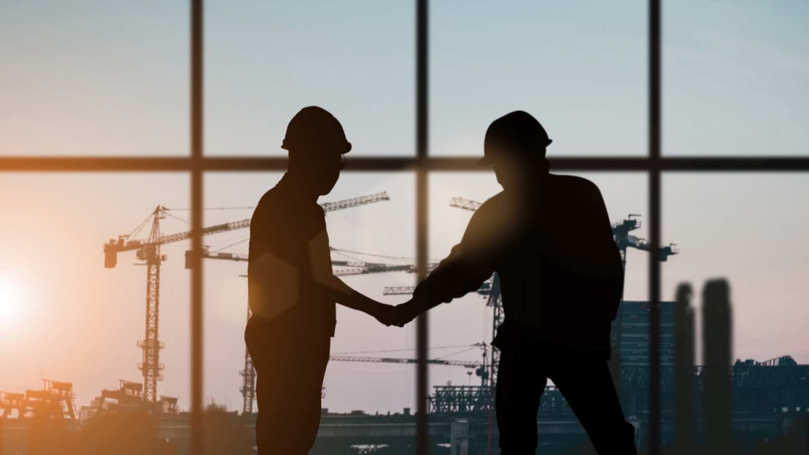 silhouetted workers shaking hands while wearing hardhats