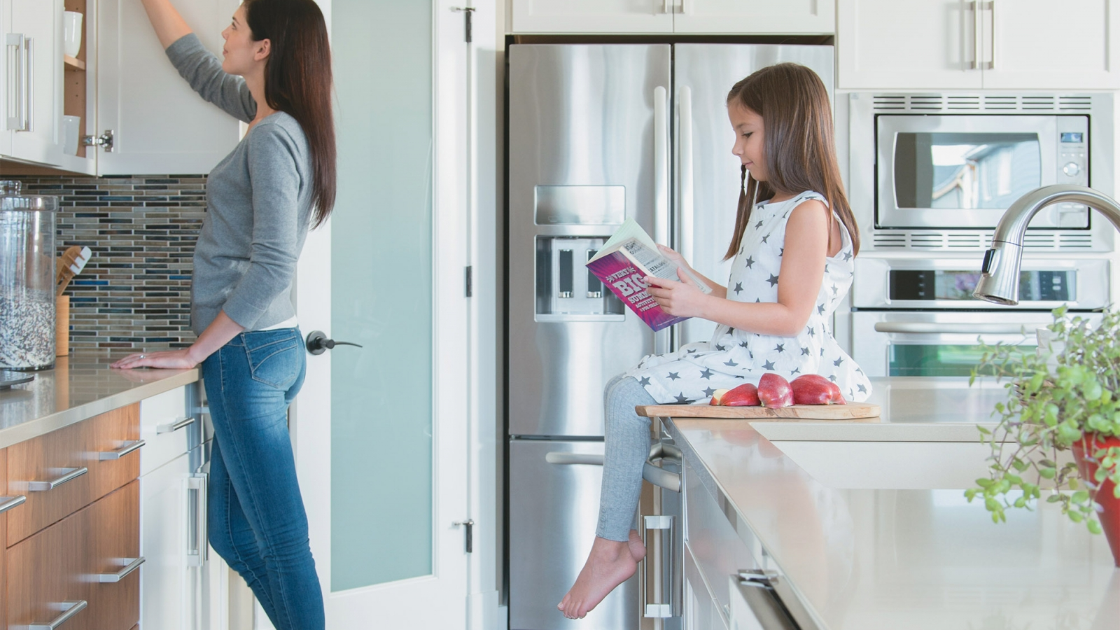 mother reaching into a kitchen cabinet while daughter sits on kitchen island reading