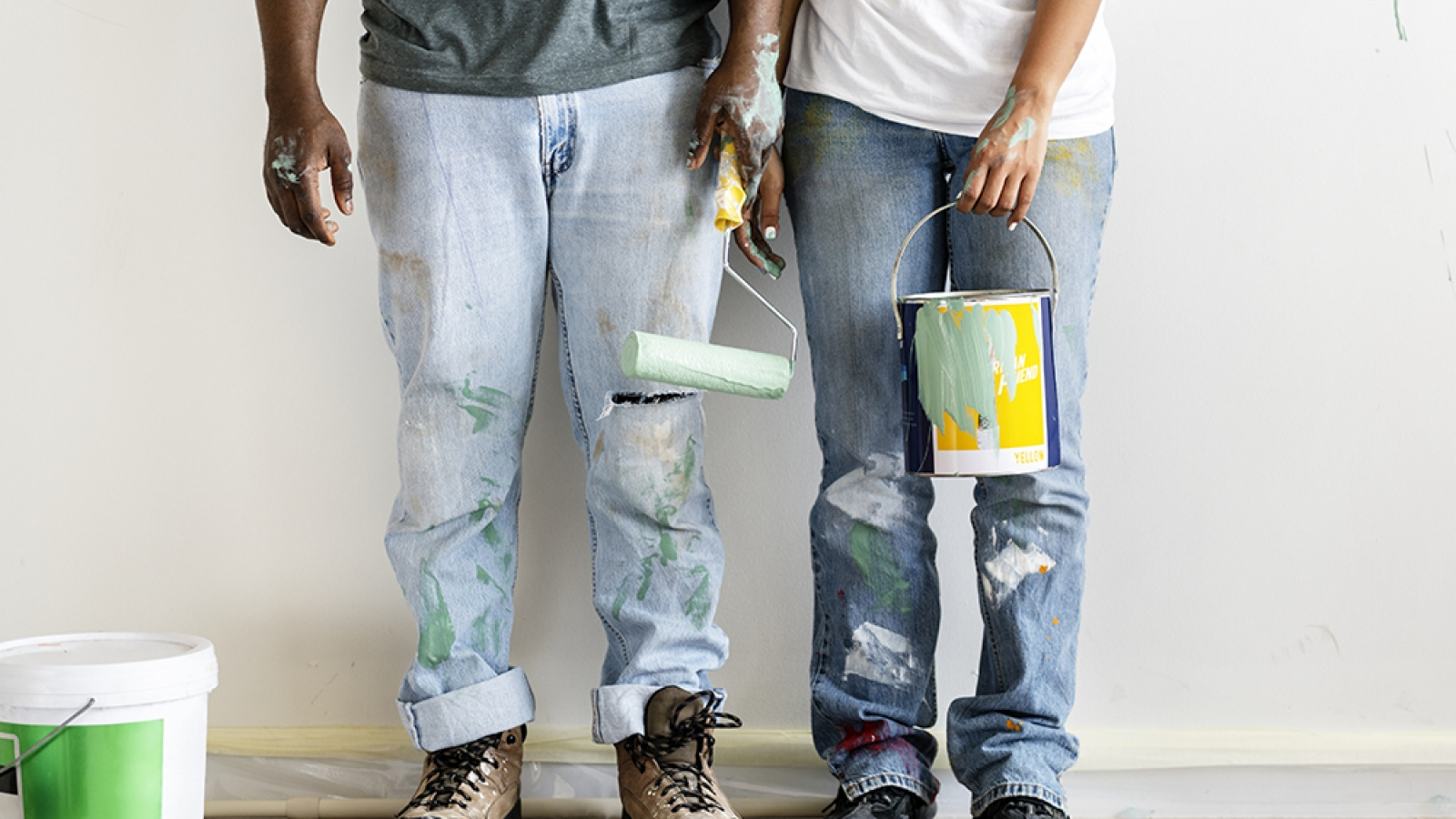Couple in jeans and boots holding a paint roller and can
