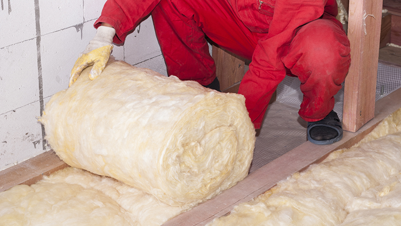 Person rolling out insulation