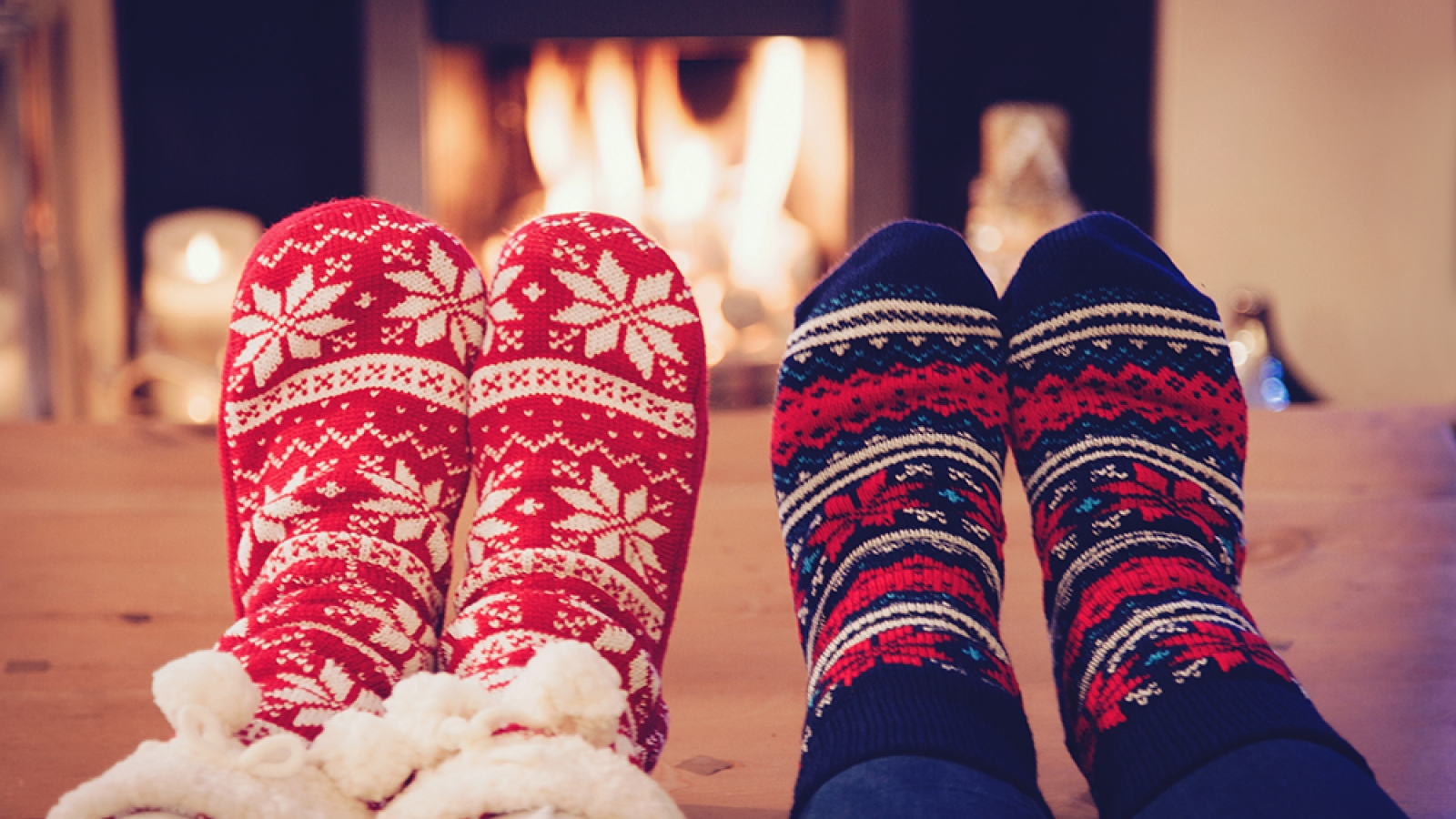 People wearing cozy socks in front of a fire