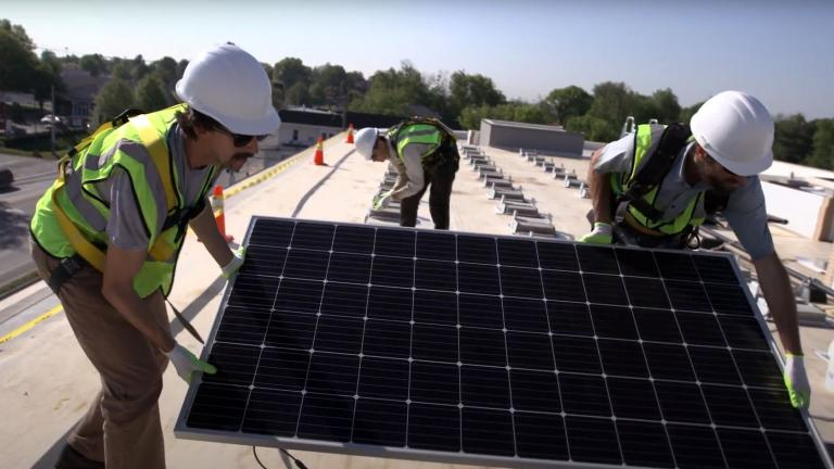 workers installing a solar panel on a roof
