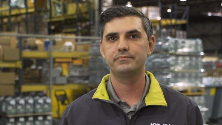 Employee standing in a storeroom with equipment in background