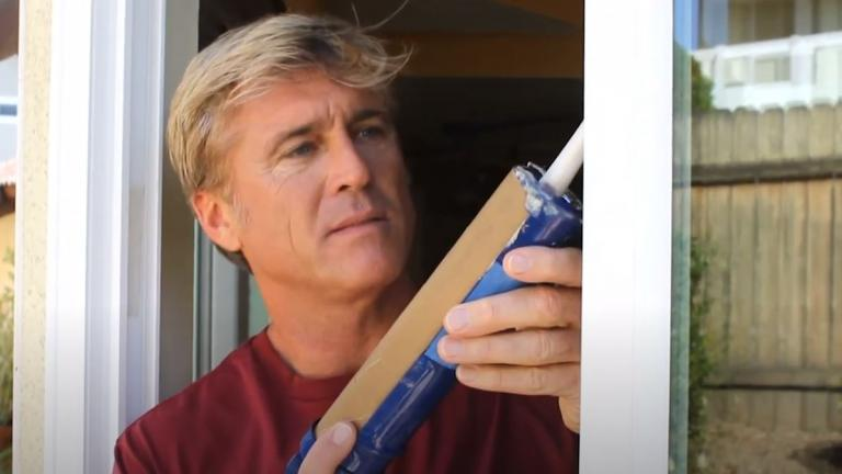 man caulking a window frame