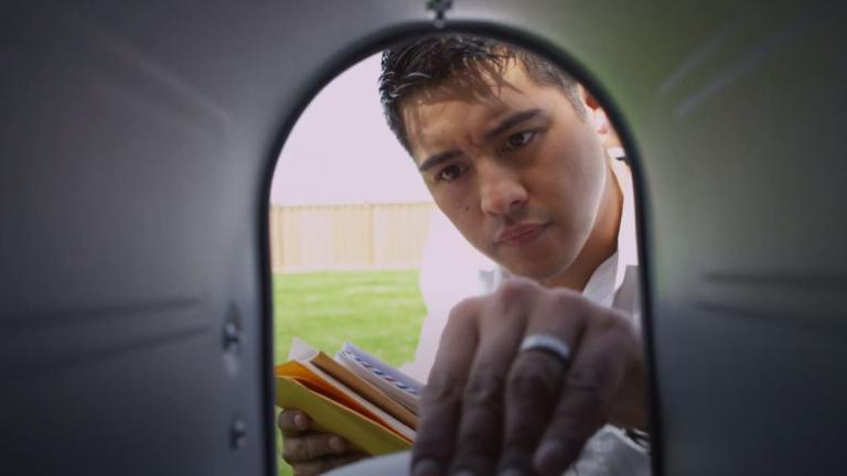 man reaching inside mailbox