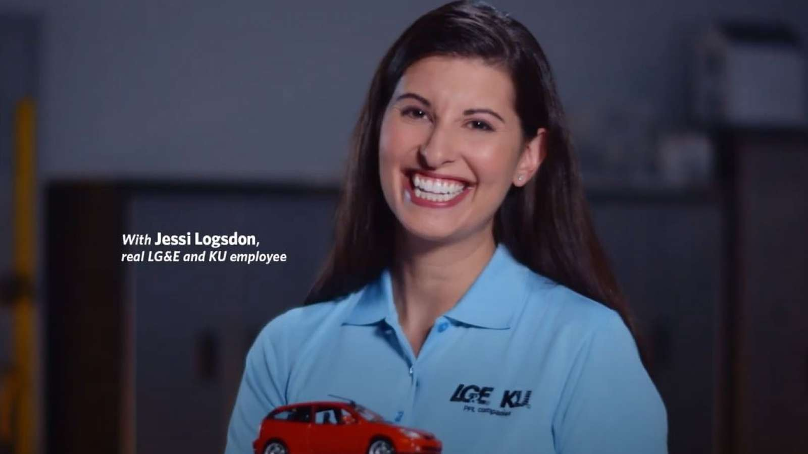 employee in blue shirt smiling and holding a model car in her hand