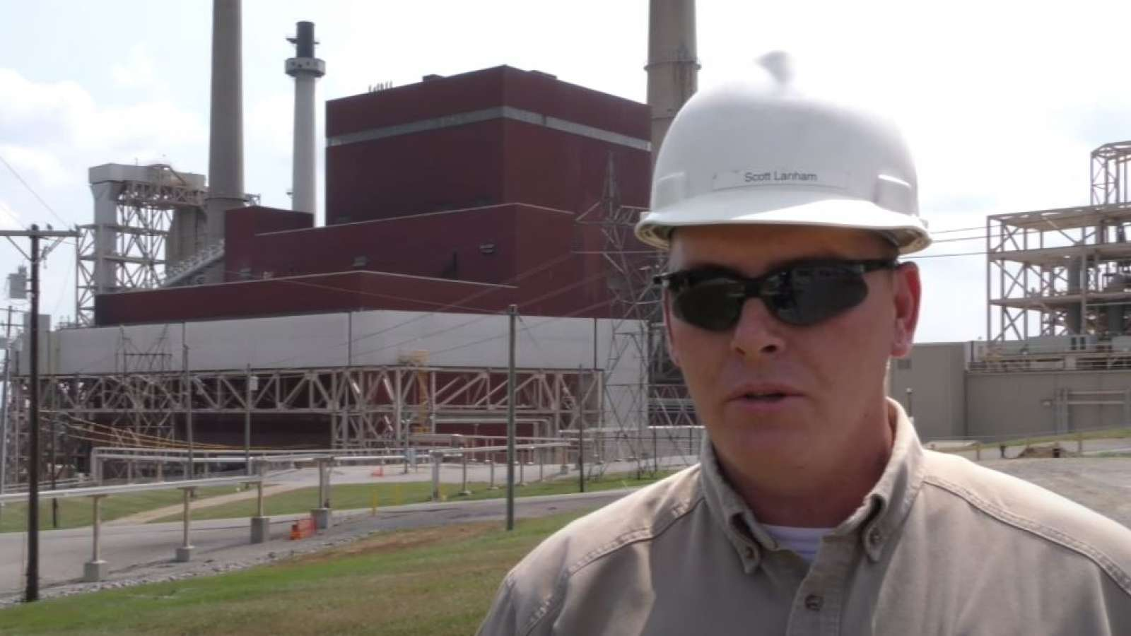employee who served in the military speaking in front of a power plant
