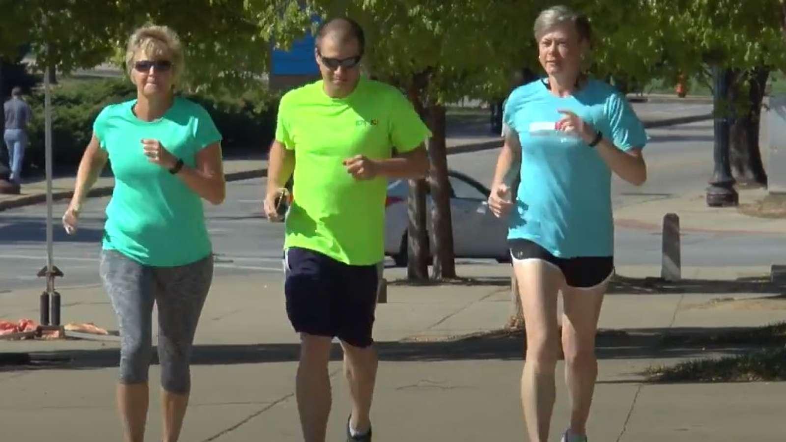 three people jogging down a sidewalk