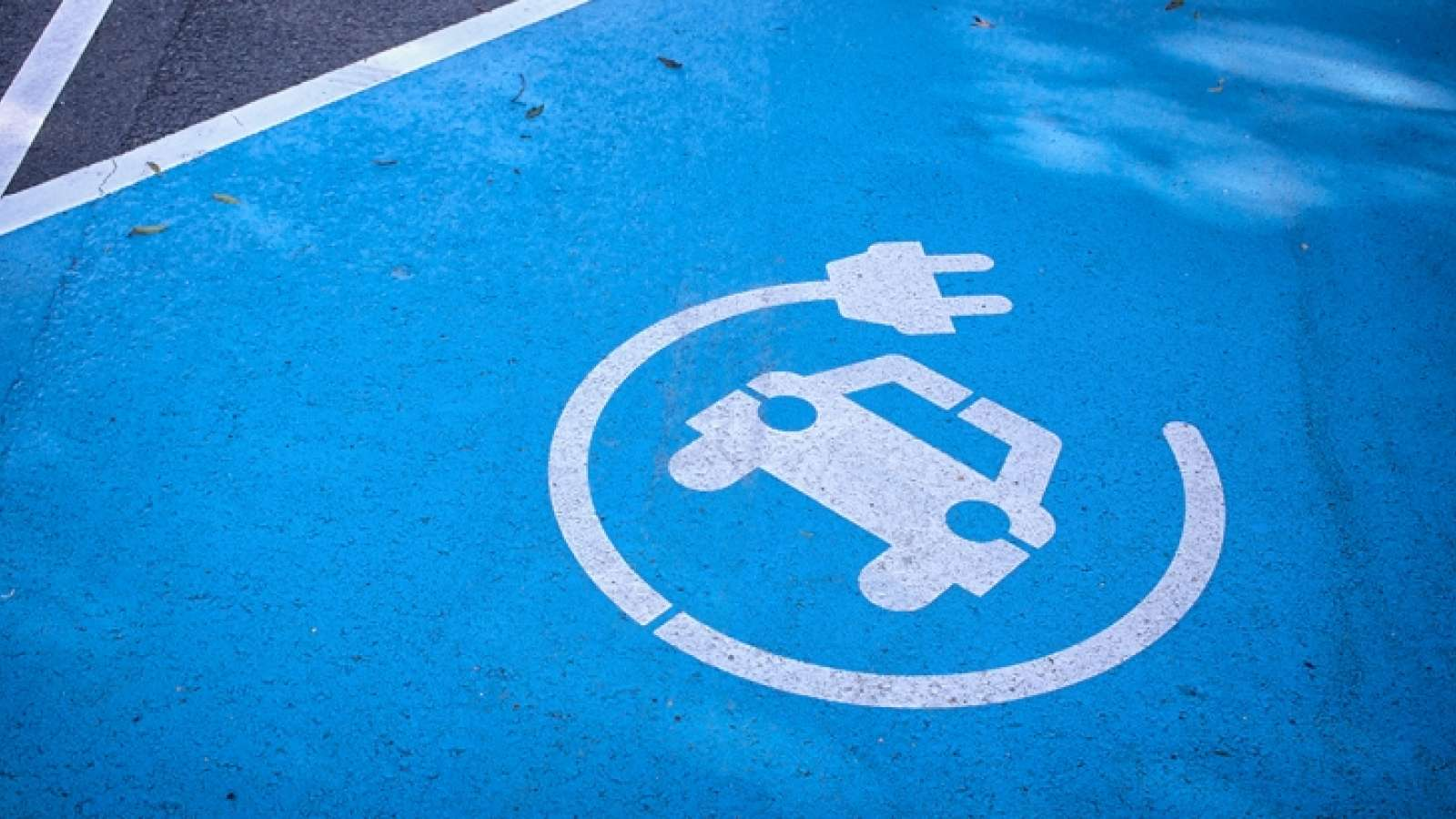a blue painted parking spot designated as a charging station