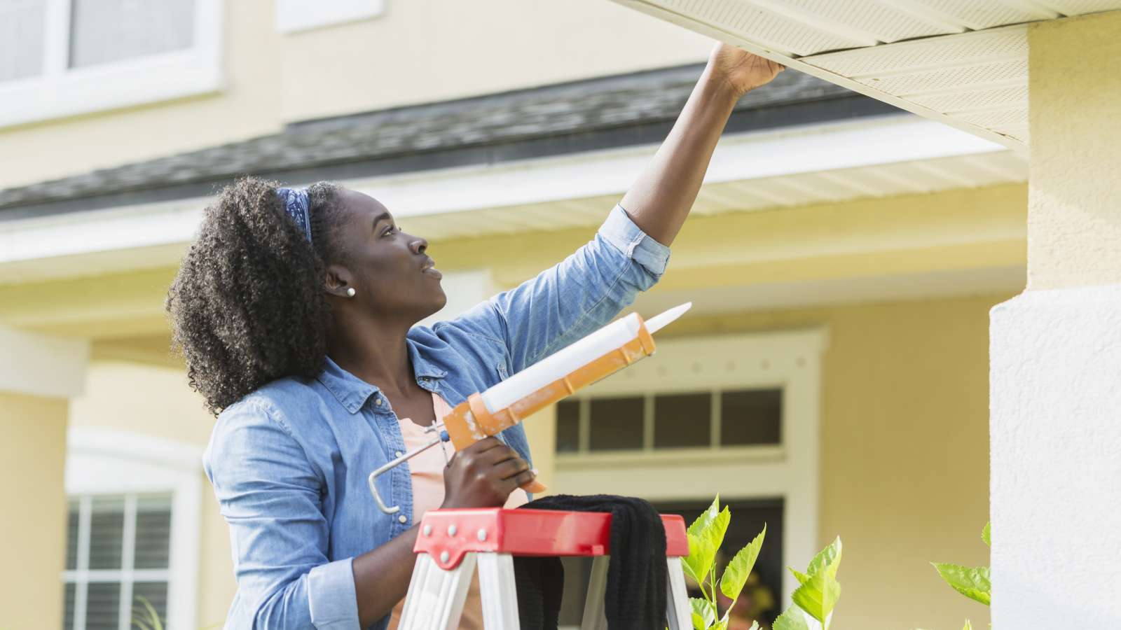 African-American female on a ladder adding caulk to home
