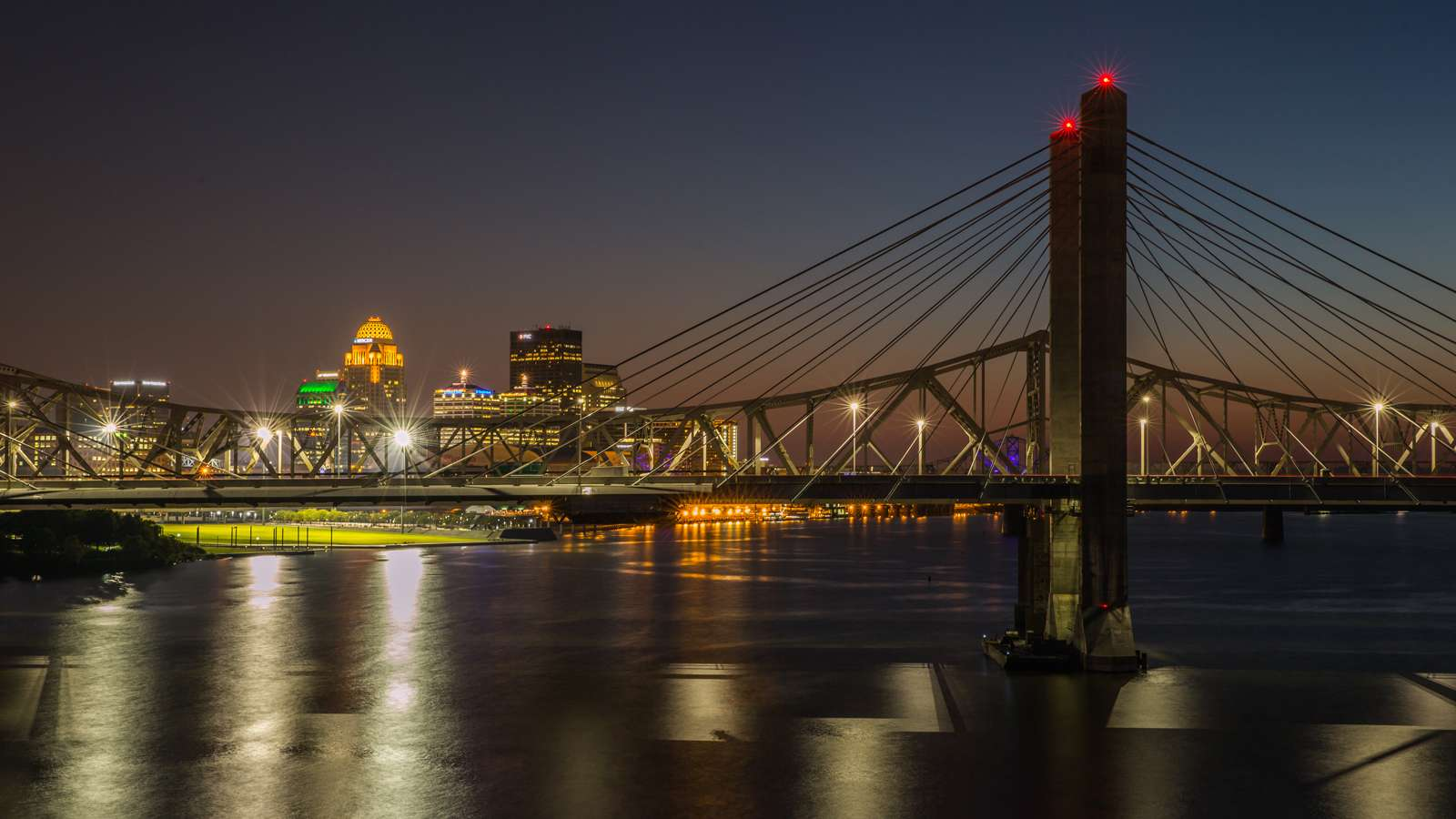 Showing the bridge downtown Louisville at night