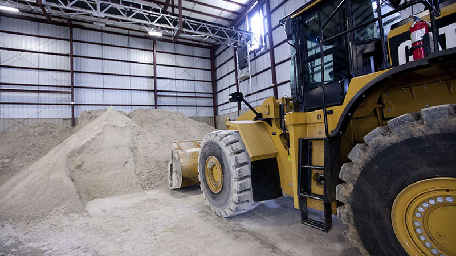 front loader scooping gypsum inside a warehouse