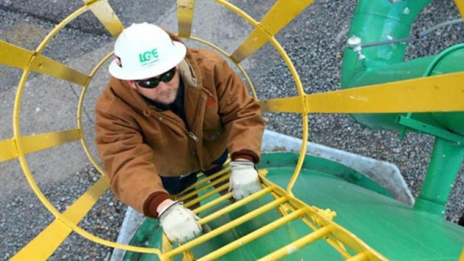 LG&E employee climbing up a safety ladder wearing hard hat