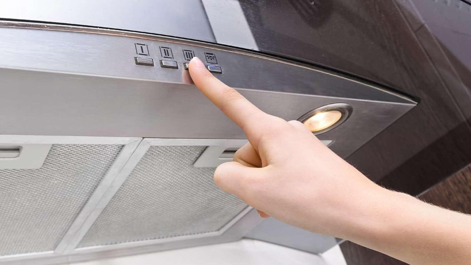 finger pressing button on an exhaust fan