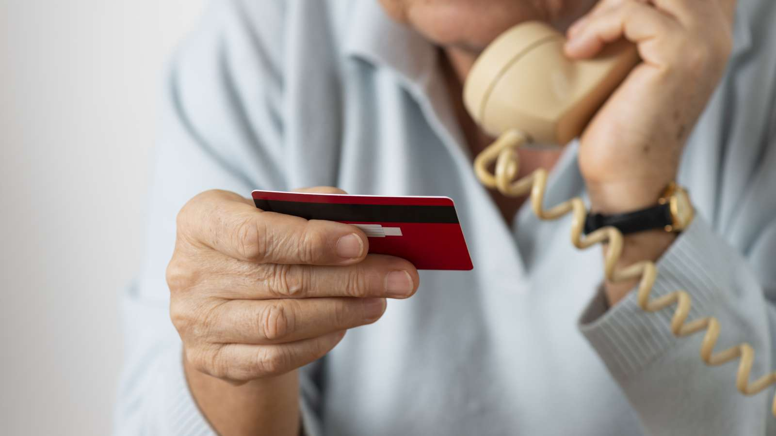 person on a phone holding a credit card