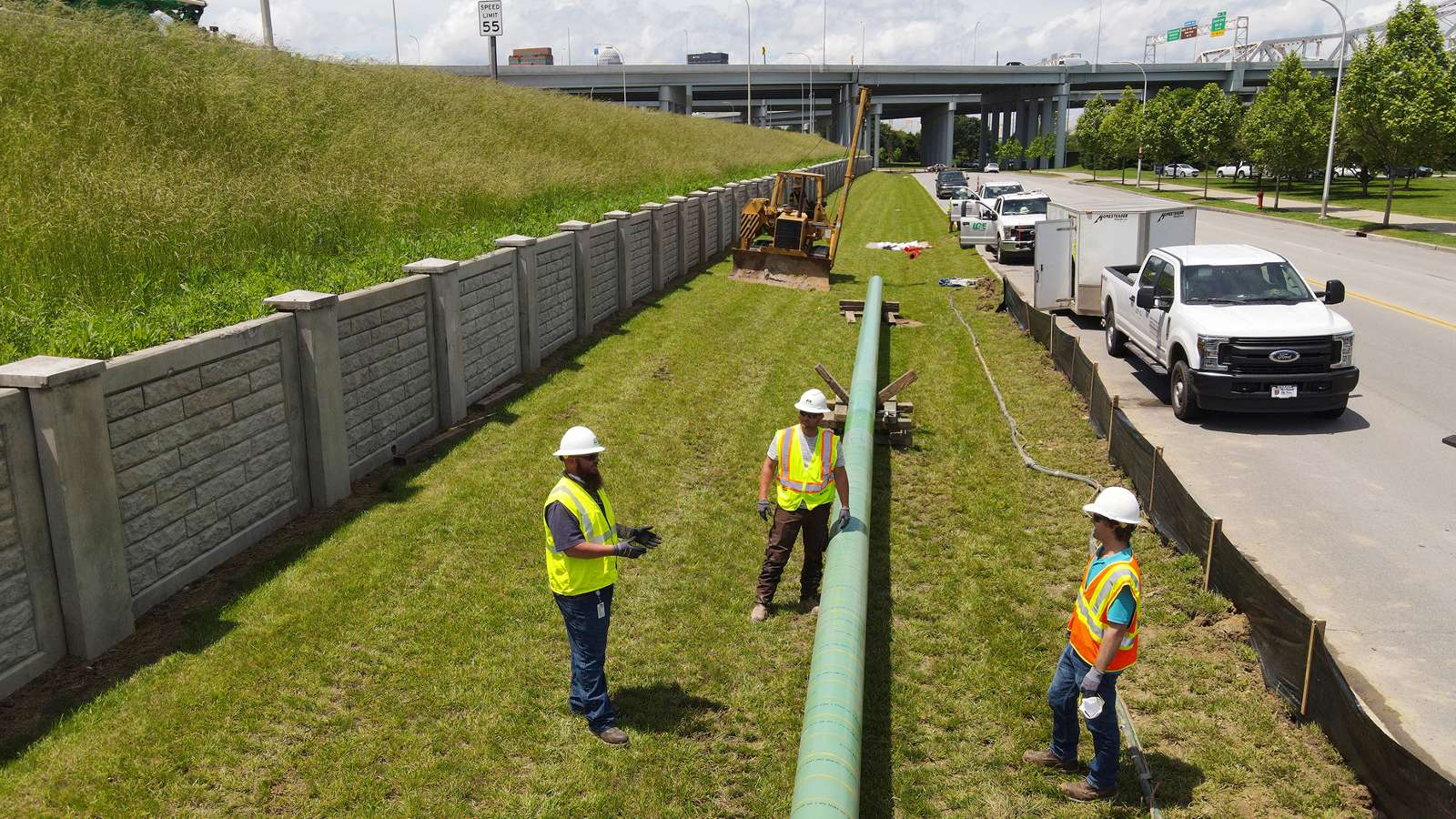 Utility workers next to a large natural gas pipe