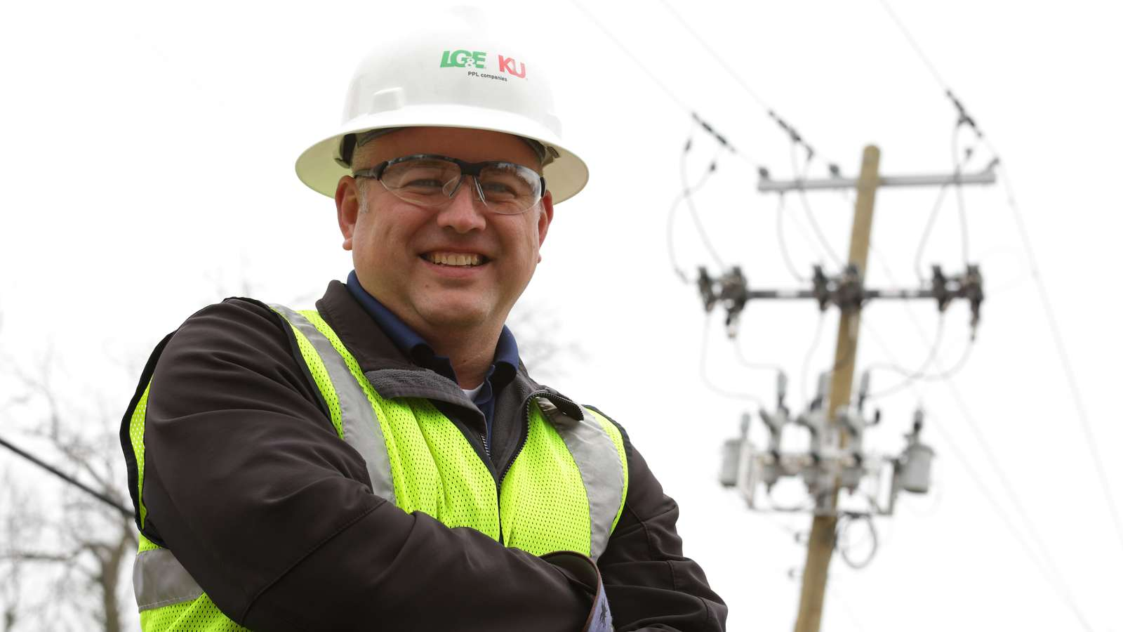 Lineman standing in front of a utility pole with reclosers