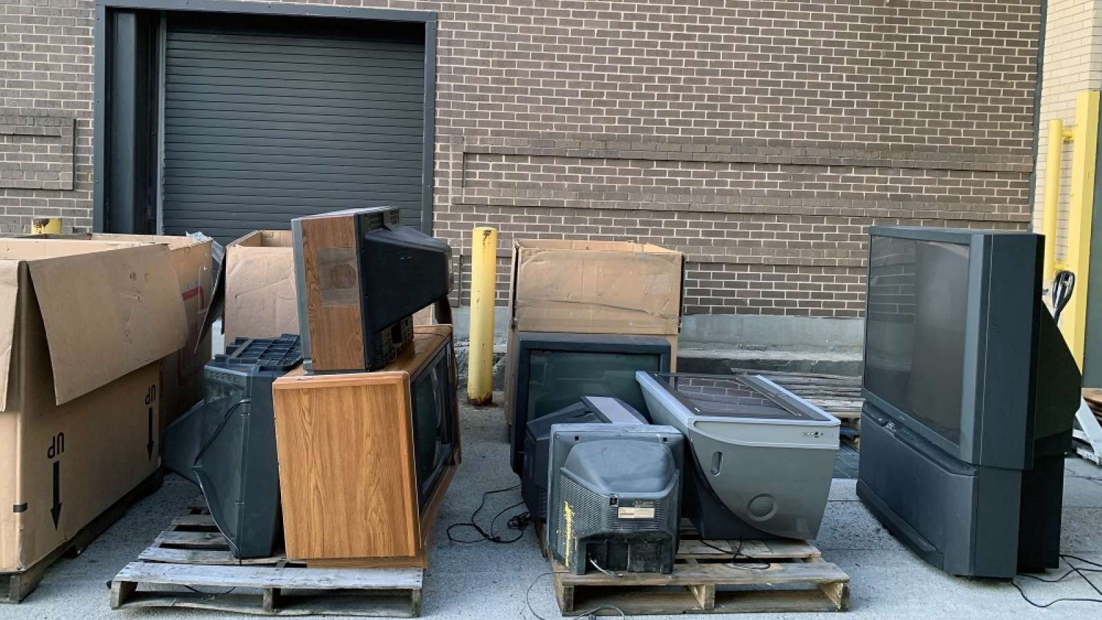 televisions on pallets at a loading dock at a recycling event
