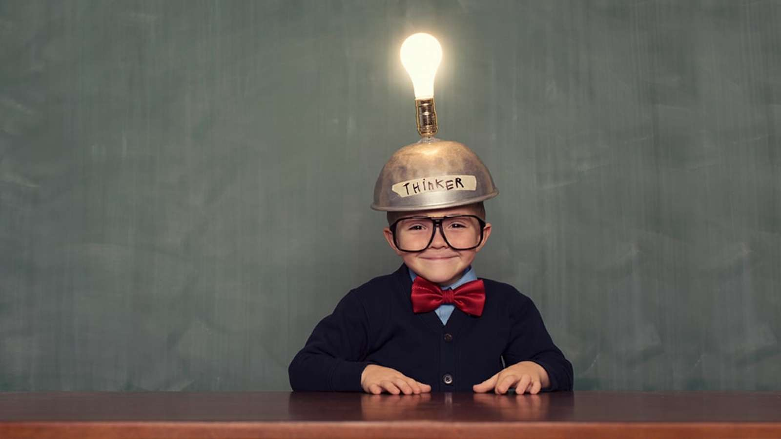 boy at table with thinker hat and light bulb