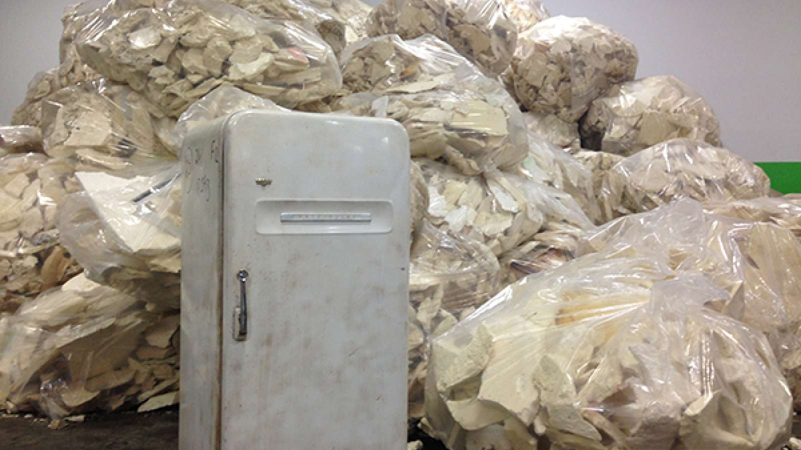 an old refrigerator in front of giant plastic bags of insulation foam