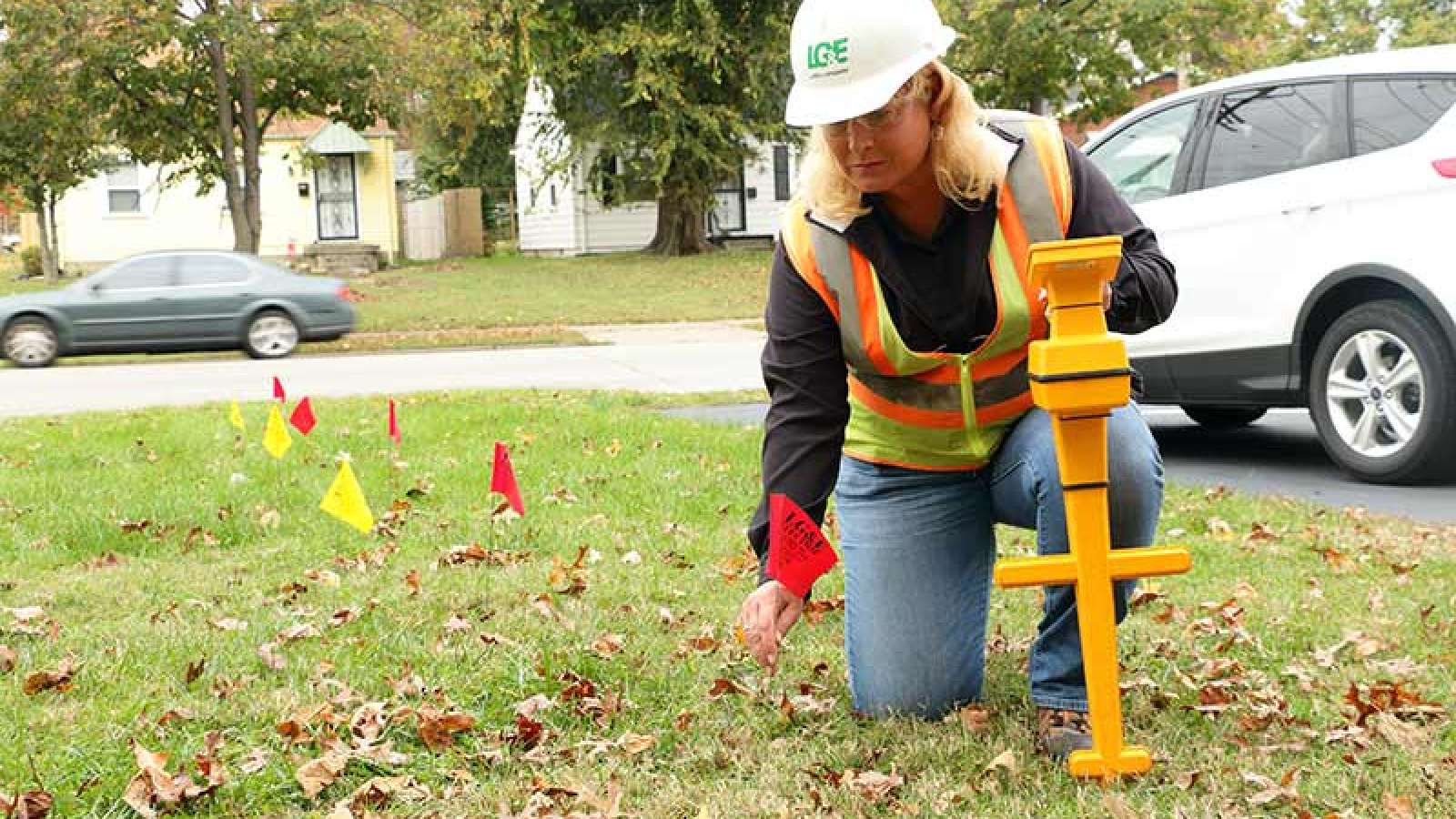 Employee placing gas line flags in yard