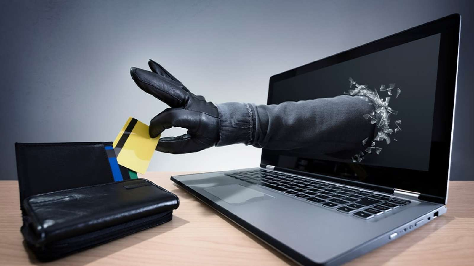 burglar arm reaches out from laptop screen to steal credit card