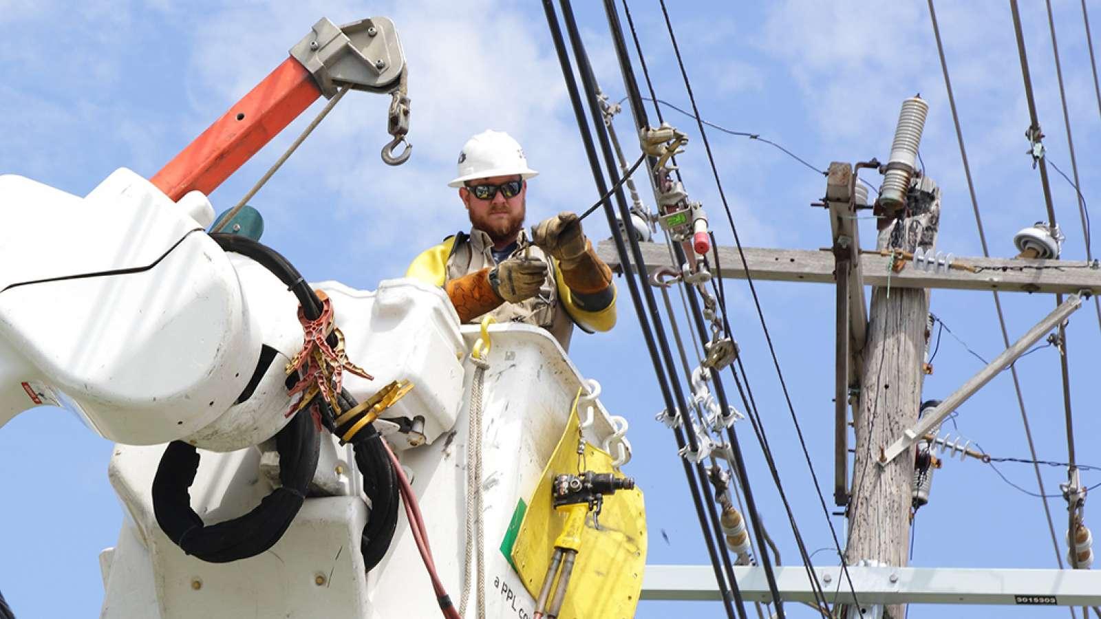 line technician in a bucket truck working on a power line