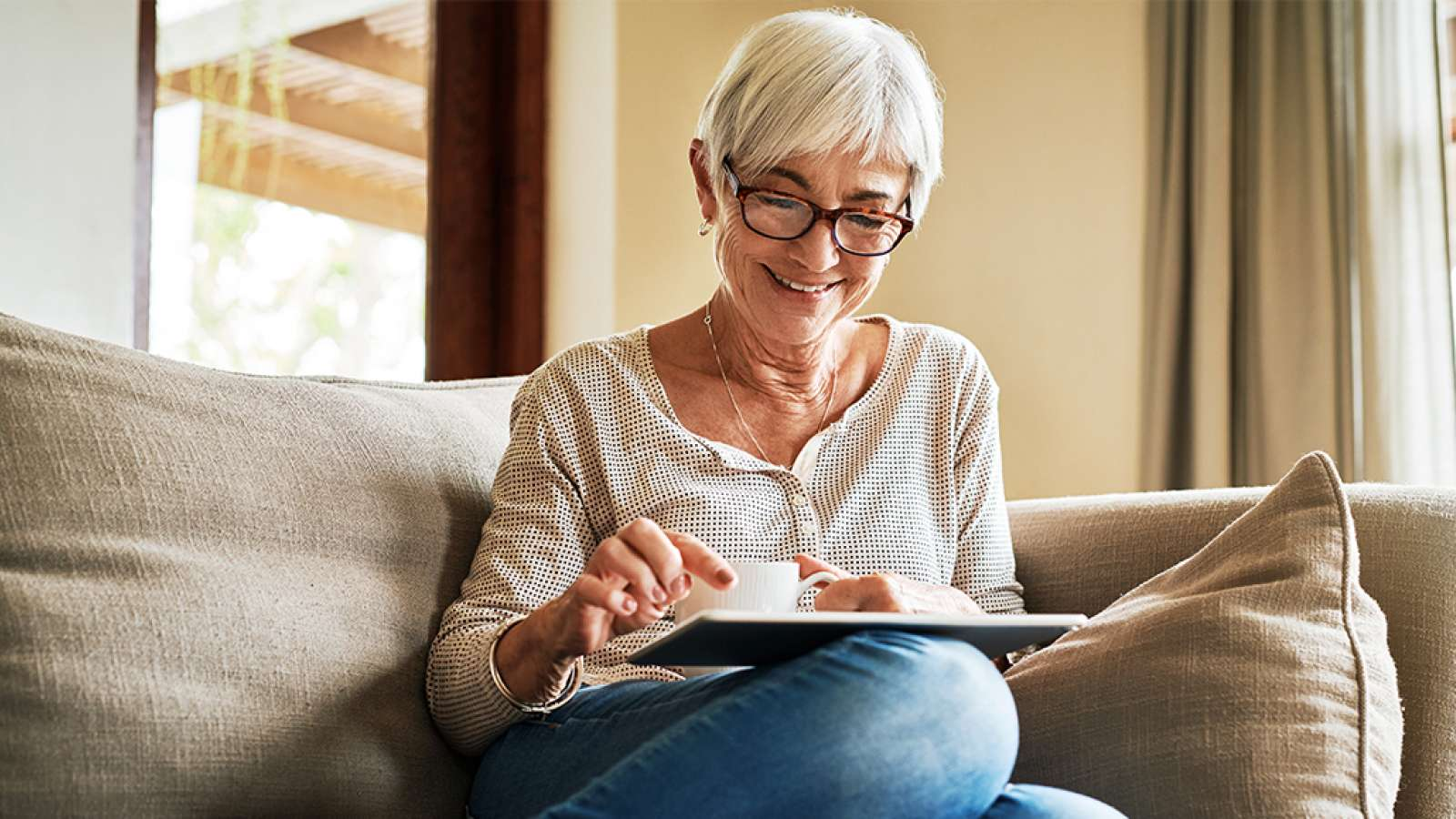 older woman sitting on a couch with coffee and iPad