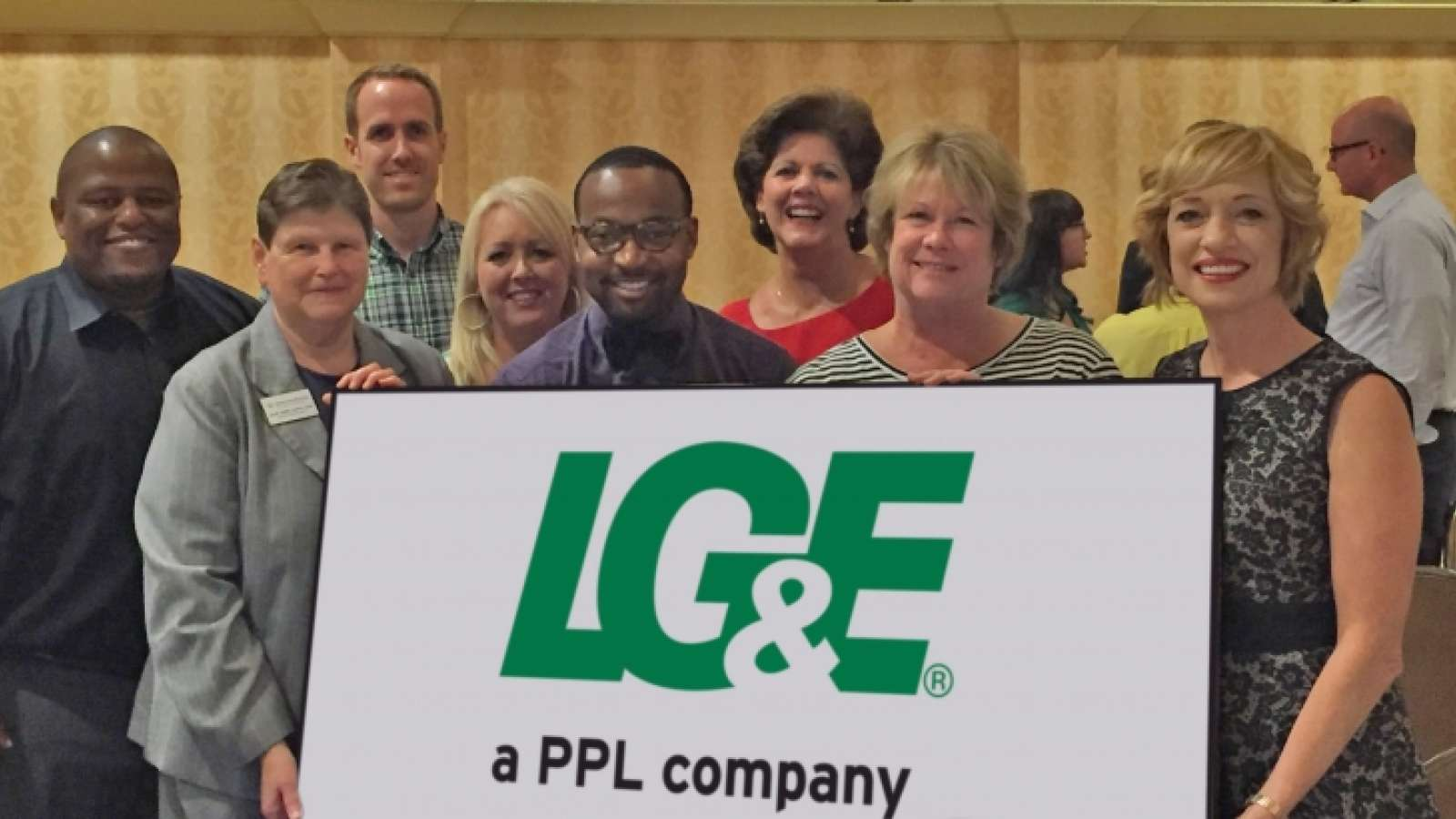 LG&E employees at a community event holding an LG&E sign