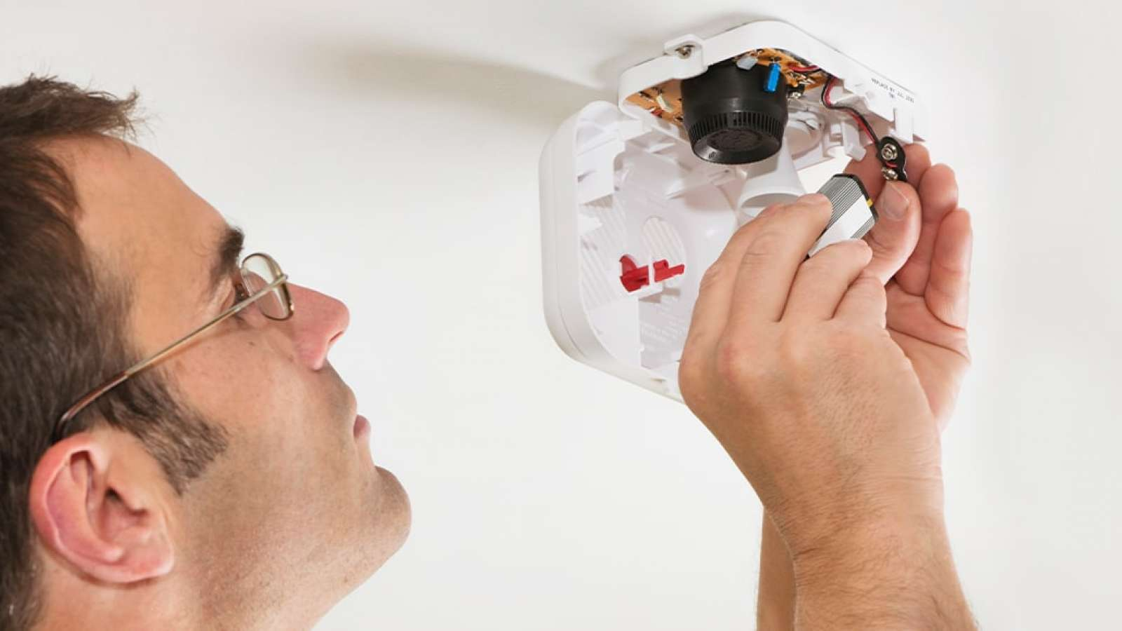 person changing battery on a smoke detector