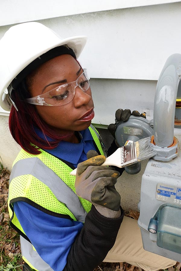 employee with PPE performing a gas leak survey on a gas meter