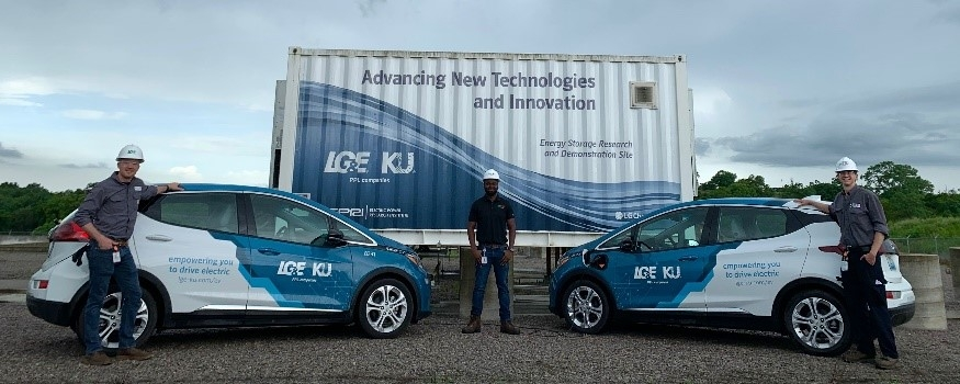 three employees with two electric vehicle and battery storage unit