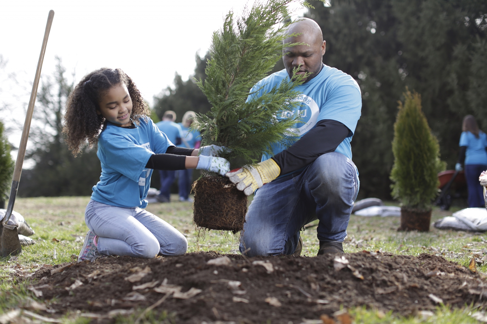 father and daughter planting a tree