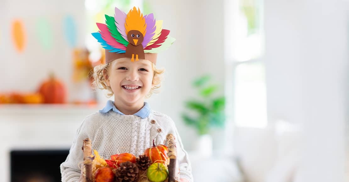 Young boy with turkey paper hat on