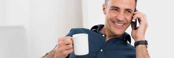 man on phone holding coffee cup