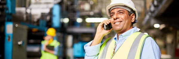 employee with hard hat on cell phone in commercial building